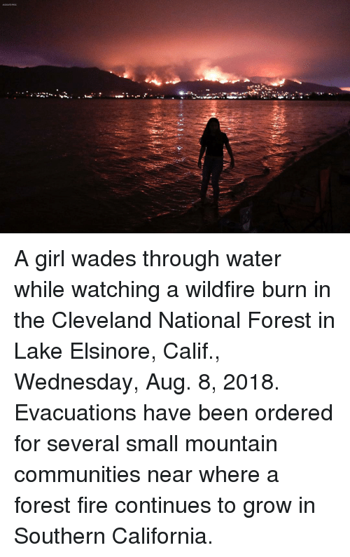Fire, Memes, and California: A girl wades through water while watching a wildfire burn in the Cleveland National Forest in Lake Elsinore, Calif., Wednesday, Aug. 8, 2018. Evacuations have been ordered for several small mountain communities near where a forest fire continues to grow in Southern California.