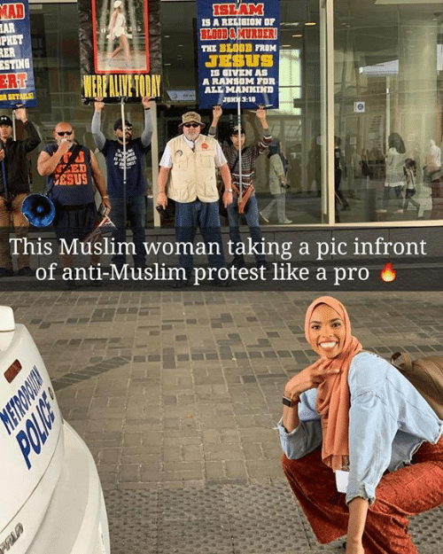 Sting: AD  AR  PHET  SLAM  IS A REIIGION OF  BLOD&MURDER  THE BLO0D FROM  JESUS  STING  ER  S GIVEN AS  A RANSOM FOR  ALL MANKIND  JONK 3:10  ESUS  This Muslim woman taking a pic infront  of anti-Muslim protest like a pro