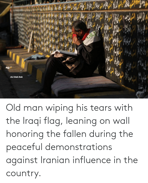 Iraqi: ALİ Dab Dab Old man wiping his tears with the Iraqi flag, leaning on wall honoring the fallen during the peaceful demonstrations against Iranian influence in the country.
