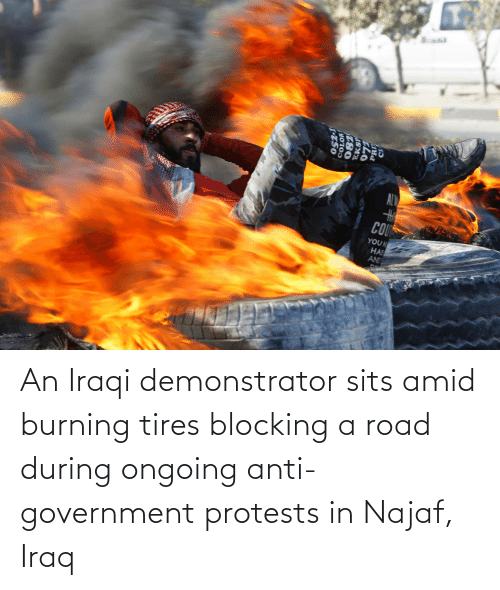 Iraqi: An Iraqi demonstrator sits amid burning tires blocking a road during ongoing anti-government protests in Najaf, Iraq