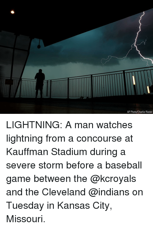 Baseball, Charlie, and Memes: AP Photo/Charlie Riedel LIGHTNING: A man watches lightning from a concourse at Kauffman Stadium during a severe storm before a baseball game between the @kcroyals and the Cleveland @indians on Tuesday in Kansas City, Missouri.