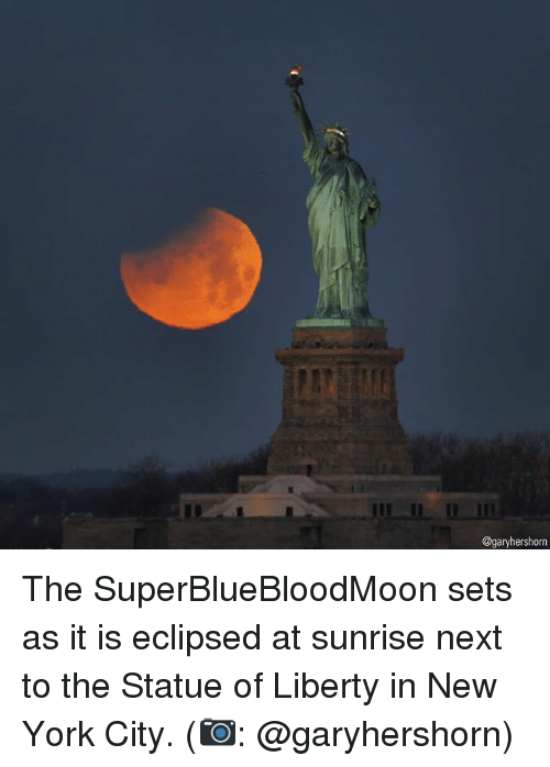 in-new-york-city: @garyhershorn The SuperBlueBloodMoon sets as it is eclipsed at sunrise next to the Statue of Liberty in New York City. (📷: @garyhershorn)