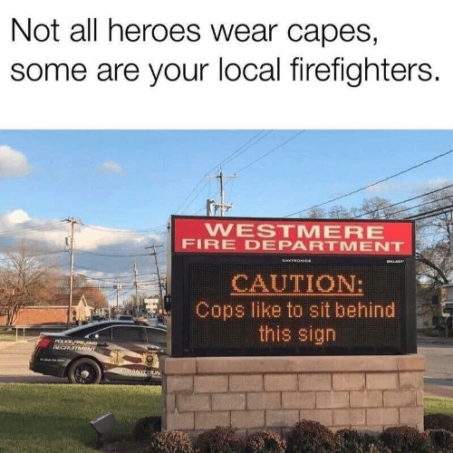Fire, Heroes, and Cops: Not all heroes wear capes,  some are your local firefighters.  WESTMERE  FIRE DEPARTMENT  DAKTRONICe  ALARY  CAUTION:  Cops like to sit behind  this sign  POUCE FRE EMS  RECRUITMENT  00COUN