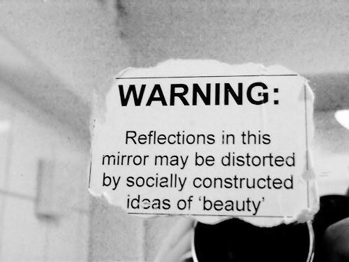 Mirror, Ideas, and May: WARNING:  Reflections in this  mirror may be distorted  |by socially constructed  ideas of 'beauty